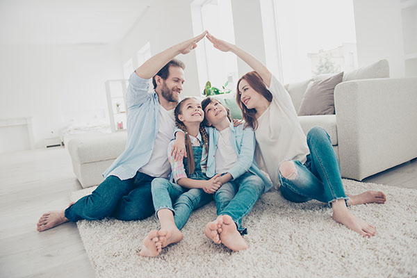 Stylish full family with two kids sitting on carpet, mom and dad making roof figure with hands arms over heads